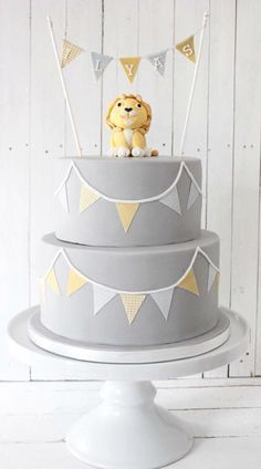 Grey and yellow lion first birthday cake with bunting by Blossom & Crumb