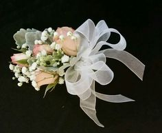 This sweet corsage exhibits blush spray roses, baby's breath and dusty miller.  It tied the mothers right in with the bridal party. To see more go to bouquetsbybecky.net. #bouquetsbybecky