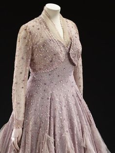 Evening dress 1948 [Jacket] Long sleeved bolero jacket of lillac tulle with an embroidered vermicular pattern, which is re-embroidered in flower shaped sequins in shades of mauve and lilac.