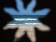 """Fotos temáticas enviadas a BBC Mundo por nuestros lectores. Más en http://www.bbc.co.uk/mundo/video_fotos/2012/10/121026_galeria_lectores_agujeritos.shtml    En esta foto de Rafael Chacón:  """"Un barco navega cerca de la costa de la Isla Margarita, en Venezuela, visto desde el agujero de una estrella recortada de una concha de coco. Al fondo, el archipiélago de Los Frailes""""."""