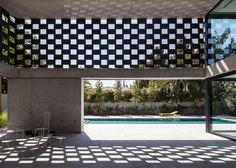Perforated screens cast graphic shadow patterns over this concrete house.