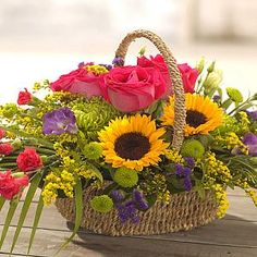 A magnificent, contemporary basket arrangement of the hottest flowers including, sunny sunflowers, hot pink roses and sweet lizzy.