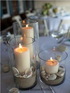 Beach sand, shells and pillar candles.