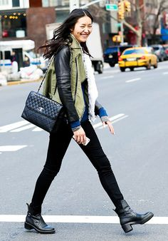 Liu Wen wears an army jacket with leather sleeves, skinny jeans, bots, and a Chanel bag