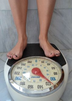 Image of a white persons bare feet on a large dial style bathroom scale