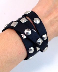 This simple but tough-talking piece promises to make an impact. A Black Wrap Leather Bracelet embellished with silver dome and pyramid studs. The studs make this bracelet perfect for punk rock and trendy closets alike. Pair this piece with your fave skinnys, and high low hem top for a hardcore timeless look! – Purity Leather Company