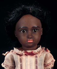"""Theriault's Rare and Beautiful German Brown-Complexioned Bisque Doll Known as """"A.T. Kestner"""" 12"""" (30 cm.) Bisque socket head with cafe-au-lait complexion,brown glass sleep eyes,black painted lashes and brows,accented nostrils,closed mouth with coral-shaded lips,pierced ears,black mohair wig,early composition and wooden fully-jointed body with straight wrists,wearing original factory chemise,shoes and socks, pierced ear holes pulled through,arms repainted. Marks: 7 circa 1884"""