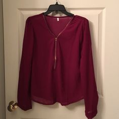 Womens cherry color blouse Womens cherry color blouse with gold zipper front. The size said XXL, but it is more like a medium to small.  Very pretty, NWOT. NEVER WORN Tops Blouses