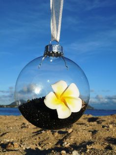 Inside this gorgeously unique Hawaiian ornament is black sand with sea shells. The ornament is highlighted with a plumeria flower handcrafted with clay. Great as a centerpiece and will give your guests something to talk about! Made in Hawaii. Add Something Aloha to your wedding!
