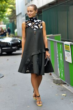 A black dress is worn over a patterned turtle neck top and paired with sandals and a black handheld clutch.