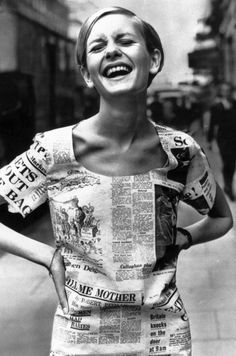 """Twiggy wears a dress fashioned from Daily Express newspapers, 1967.She painted on eyelashes under her eyes so as to resemble a porcelain doll and had her hair cut short. The photographer Barry Lategan took a picture for the salon, and, by chance, the fashion editor Deirdre McSharry saw it. In the February 1966 issue of the Daily Express, she used a center spread to portray this """"Cockney Kid"""" as """"the Face of '66."""""""