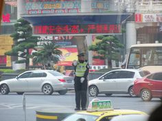 Policeman directing traffic in his little circle. Chongqing, China.