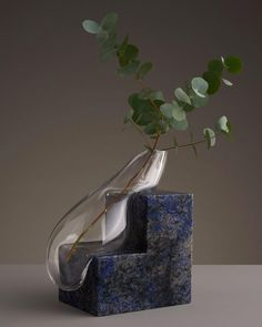 """Stockholm-based designer Erik Olovsson created this amazing series of """"melting"""" vases, combining smooth hand-blown glass pieces with geometric slabs of stone.  """"The designs can serve either as decorative sculptures or functional holders for flowers or sprigs of greenery. Olovsson explains that each one is intended to explore the relationship between space and object through an interplay of stark contrasts: the transparent versus the opaque, the geometric versus the organic, the..."""