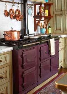 The new aubergine Aga stove has three ovens, each maintaining heat for a specific function: roasting, baking, or simmering.  Two hot plates—one set for boiling, one for simmering—are on the cooktop.