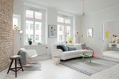 salon scandinave, chaise blanche avec pieds en bois et métal, murs en briques, canapé blanc avec coussins décoratifs