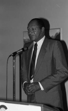 Tom Bradley standing in front of a microphone. Photo by Guy Crowder.