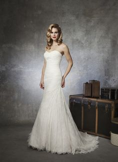 Justin Alexander wedding dresses style 8657 A Chantilly lace sweetheart neckline, and ruched bodice going into an  asymmetrical draped mermaid gown. Style is delicately beaded with  sequins and has a Chantilly lace hem. Buttons cover the back zipper and  this style has a chapel length train.