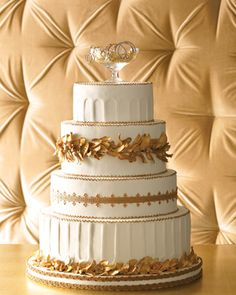 """Wedding Cake with Golden Flowers and Foliage    Grecian Gold headdresses of flowers and foliage made their mark during the Hellenistic period, and here, they make for a fitting cake motif. Made of gum-paste flowers painted with gold luster dust, the wreaths, along with the Corinthian column-inspired tiers, turn this cake into a Greek fantasy. Encircled in real ribbon and topped with a champagne coupe bubbling over with a necklace, of course. """"Trinity Crash"""" necklace, Cartier."""