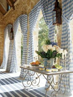 The blue and white curtains softens the stone wall, adds color and with tiebacks anchored high lets the light in.