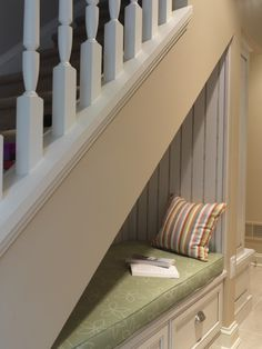 Reading nook tucked under the stairs with storage drawers below the cushioned seat