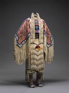 Woman's Dress and Accessories Jodi Archambault Gillette (American, born 1959) Date: 2005 Medium: Native tanned and commercial leather, glass and metal beads, cotton cloth, silk, dentalium shell, metal cones, horsehair, plastic, hair pipes, brass bells, porcupine quills, brass tacks, brass and metal studs, silver cones