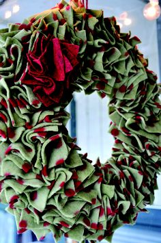 Fleece Wreath: cut squares of the fleece, and layered them into piles of two, then stuck each straight pin through the center of the squares and into the foam.