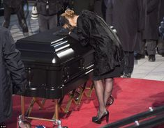 No words: Celine lays her head on the coffin during the ceremony standing alone with her h...