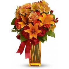 A gift of floral fire, ablaze with the warmth of radiant orange roses and lilies stunningly arranged in a dazzling orange vase.The exciting bouquet includes orange Asiatic lilies, orange spray roses, orange roses, red carnations and orange alstroemeria accented with assorted greenery and a scarlet ribbon