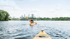 Kayakers on river against Minneapolis skyline