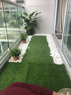 Tiny balcony with artificial grass and river pebbles