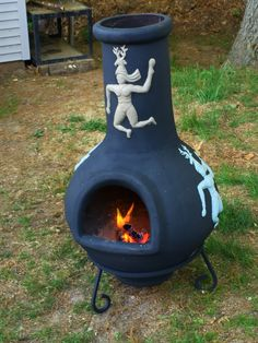 """My weekend art project, took an old clay chiminea that was """"well"""" used. Used high heat black paint & leftover paint from the house. Still usable! Mission accomplished!!!!!"""