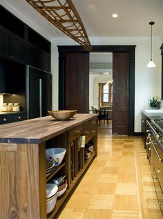 Brooklyn brownstone kitchen with black cabinets brass hardware and wood shell of canoe