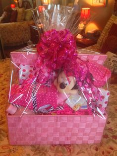 Another Baby Shower creation. I went with a Minnie Mouse theme.  I found the basket, tissue paper & ribbon at Hobby Lobby. I bought my gifts from The Disney website and a blanket and hat personalized so mom could keep them as keepsakes. All gifts were wrapped in tissue paper and tied with coordinated ribbon Added a stuffed Minnie Mouse from Babies R Us.