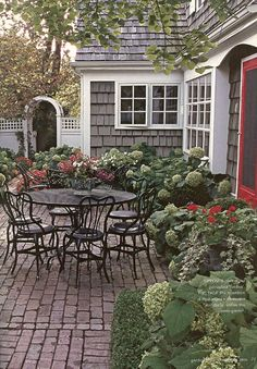 Great shake house with hydrangeas, old brick patio, and fence & arbor.