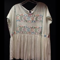 Free People Flowy Top Gorgeous white/Ivory top with tribal design. Oversized and fits size 4-12. This top is a great bargain because it does have a small stain on front and the string came out a tad. Stain isn't too noticeable while wearing though. This top is a must have. Free People Tops