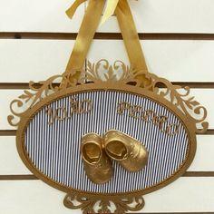 Quadro oval para porta de maternidade em MDF, pintado em ouro velho, com aplique de sapatinho em resina. <br>O tecido pode ser escolhido pela mãe, de acordo com a decoração do quarto do bebê. Acabamento em fio de seda ou pérolas para meninas.