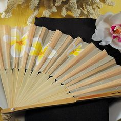 Elegant folding hand fans feature tropical white and yellow Plumeria floral print on satin fabric over bamboo ribbing. Sold in sets of 6