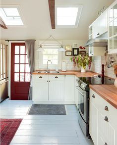 white kitchen with butcher block counters. Blue floor. Red door.  Example to see that the blue gray walls with white cabinets and trim and red and black accents totally would work!!!