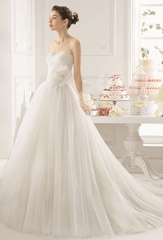 Brides: Aire Barcelona. Beaded tulle and lace dress with flower in a natural color.