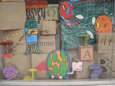 Whimsical display using cardboard boxes. #Merchandising inspiration for back-to-school #eyewear window display.