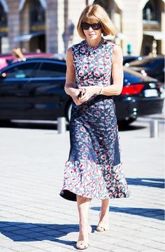 Anna Wintour wears a floral Christian Dior midi dress with nude heels and Chanel sunglasses
