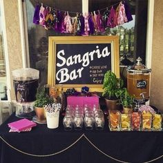 a sangria bar in black, pink and purple with a bead garland and a tassel one