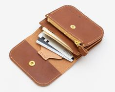 収納したカードを簡単に取り出すためのPULLタブが印象的なハンドメイドの革財布。ポケットに納まり持ち歩けるコンパクトなサイズですが、お札、コイン、カードなど、必要なものは一通り収納できます。