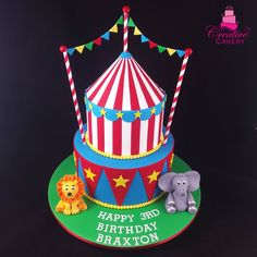 Circus cake / Carnival cake. This adorable circus themed cake was a chocolate mud cake with dark chocolate ganache made with Callebaut couverture chocolate. Decorated with edible hand sculpted fondant elephant and lion animals and edible colourful flags. This brightly coloured cake included a circus tent in traditional red and white fondant stripes and was presented on a green fondant covered board. #creativecakeryadelaide #birthdaycake #circuscake