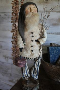 cinnamon creek dry goods | 2015 | Ticking Pants Santa... This fine fellow stands 21'' tall standing on his log base. He has a chalkware face, brownish green stocking cap, batting jacket with tiny bell buttons, vintage blue ticking pants and holds a bundle of twigs in one arm and a red paper pantry box in the other. 125.00 plus shipping...SOLD
