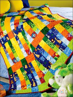 "Rainbow Baby Quilt-Brightly colored fabric strips make up the simple blocks in this eye-catching quilt. It's a great way to add color to Baby's room. This e-pattern was originally published in Weekend Quilting Wonders.  Size: 50 1/2"" x 55"". Skill Level: Beginner Designed by Connie Rand"