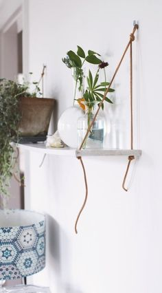 Make your own simple shelf with a leather cord and wooden board.