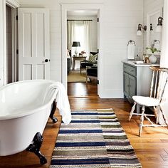 "Layer color and pattern underfoot.   A large woven rug carries the bedroom's neutral palette into the bath and adds both softness and practicality.    Soak in classic farmhouse style.   A deep, cast-iron, claw-foot tub is only natural in a house like this. ""Even though it's new, it looks like it's always been here,"" says designer Paige Schnell."