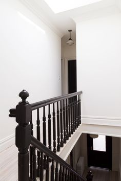 White Arrow renovates Queens rowhouse with navy millwork and modernist furniture Black Painted Stairs, Dark Staircase, Black Stair Railing, Interior Stair Railing, Black Stairs, Staircase Railings, Banisters, Staircase Design, Spiral Staircases