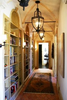Interesting ceiling and pendants over arched bookcases and terra cotta floor, rug